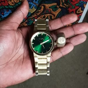 Gold round bezel Nixon watch and 18k gold ring